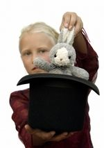young magician pulling a rabbit out of a hat